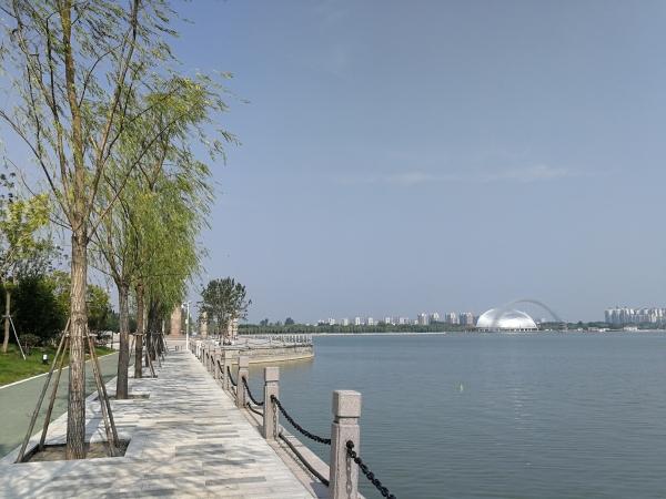 備受市民關注的聊城東昌湖景觀提升工程進展情況如何?近日,不少聊城的市民已經看到了答案,有的市民已經開始享用東昌湖邊的新建步行道和自行車道。聊城東昌湖景觀提升及游路改造工程是從去年6月份開始破土動工,近一年內,東昌湖邊上都被圍擋隔離。日前,筆者來到東昌湖邊,看到湖邊的圍擋大部分拆除,很多廣場和環湖路已經開放,湖邊樹木叢生、鮮花斗艷,市民可以悠閑地暢游東昌湖畔。  現在湖邊已經大變樣了,和一年前相比漂亮了很多,公共設施也很齊全,而且還很現代化,這些紅色和綠色的道路鋪的真好,平時沿著湖邊散散步,騎騎自行車很