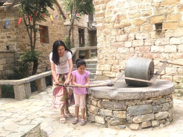 """一对母女游客在山东省莱芜市雪野旅游区""""一线五村""""卧云铺景区体验古村"""